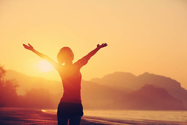 cheering woman open arms to sunrise at seaside cheering woman open arms to sunrise at seaside arms outstretched stock pictures, royalty-free photos & images
