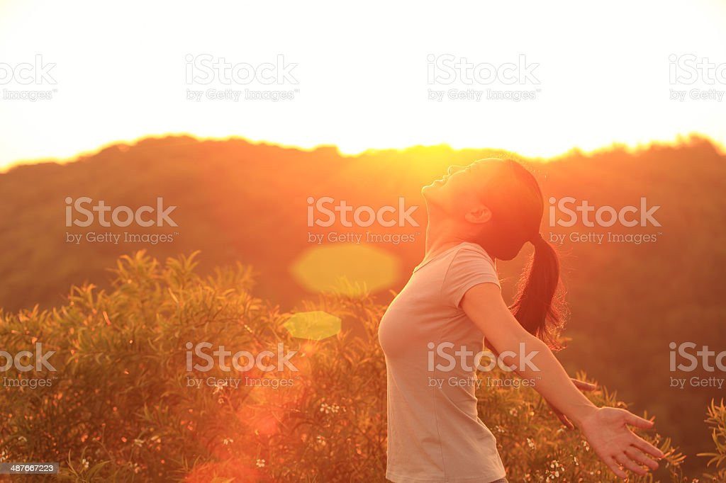 cheering woman open arms to sunrise stock photo