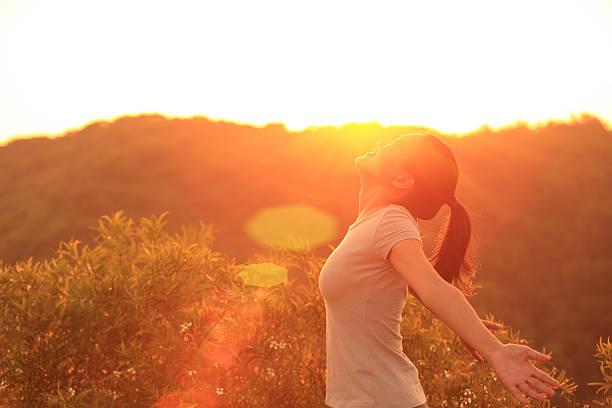 jubeln frau offenen armen zu sonnenaufgang - damen top gold stock-fotos und bilder