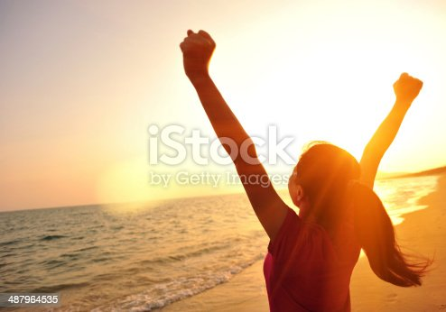 istock cheering woman open arms to sunset at seaside 487964535