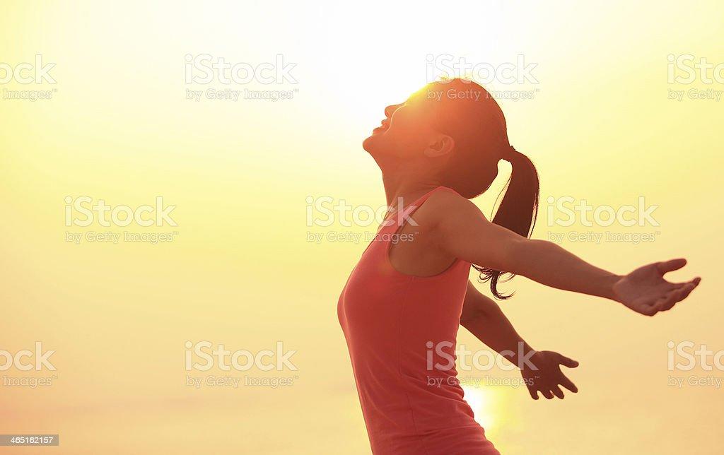 cheering woman open arms under  sunrise on beach stock photo