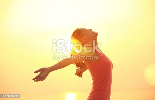 istock cheering woman open arms under  sunrise on beach 487648969