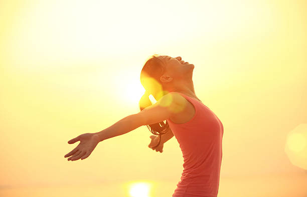 cheering woman open arms under  sunrise on beach - arms outstretched stock photos and pictures