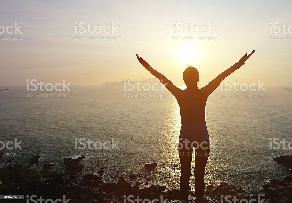cheering woman sunrise seaside stock photo