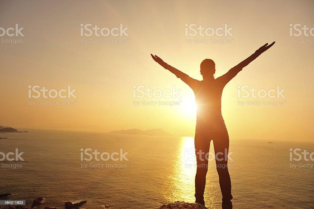 cheering  woman sunrise seaside stock photo