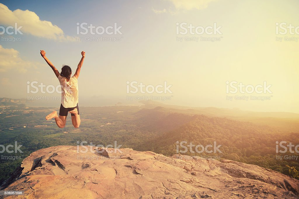 cheering young asian woman jumping on mountain peak rock stock photo
