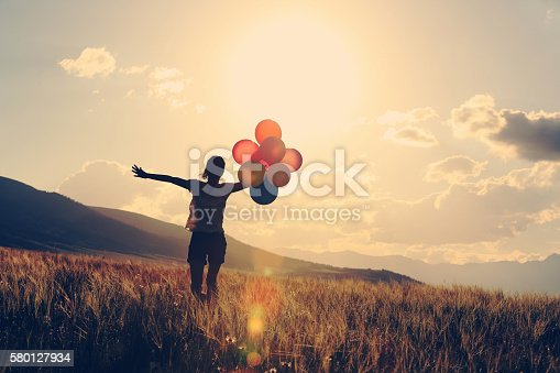 637457536 istock photo cheering young asian woman on grassland with colored balloons 580127934