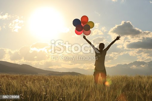 637457536 istock photo cheering young asian woman on grassland with colored balloons 580128958