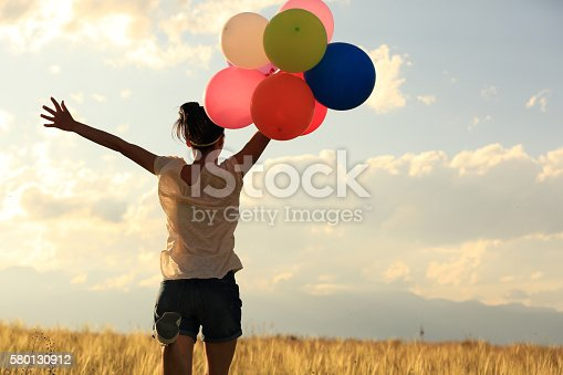 637457536 istock photo cheering young asian woman on grassland with colored balloons 580130912