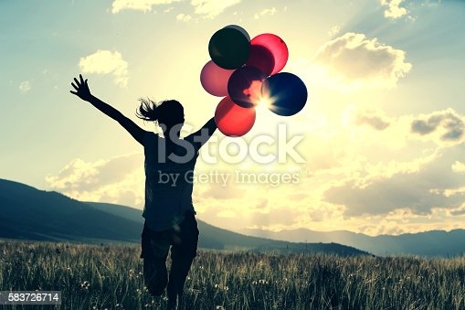 637457536 istock photo cheering young asian woman on grassland with colored balloons 583726714
