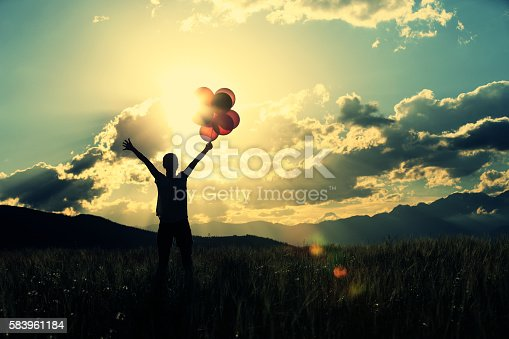 637457536 istock photo cheering young asian woman on grassland with colored balloons 583961184