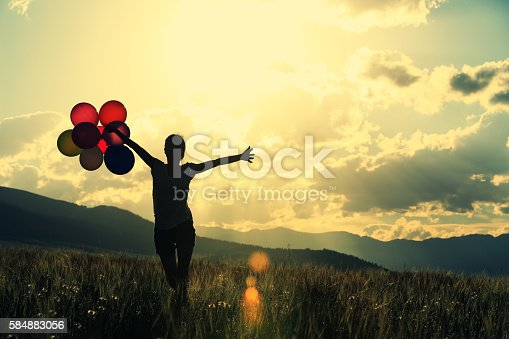 637457536 istock photo cheering young asian woman on grassland with colored balloons 584883056