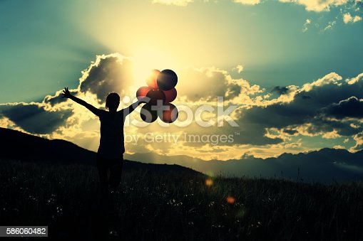 637457536 istock photo cheering young asian woman on grassland with colored balloons 586060482