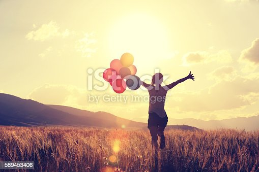 istock cheering young asian woman on grassland with colored balloons 589453406