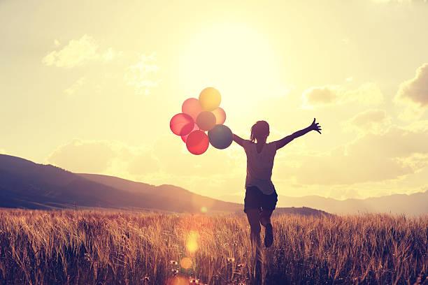 jubelnde junge asiatische frau auf grasland mit farbigen ballons - joggerin stock-fotos und bilder