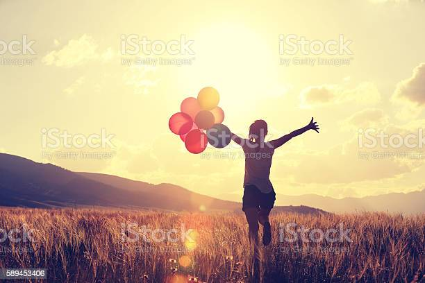 Photo of cheering young asian woman on grassland with colored balloons