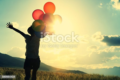 637457536 istock photo cheering young asian woman on grassland with colored balloons 589964404