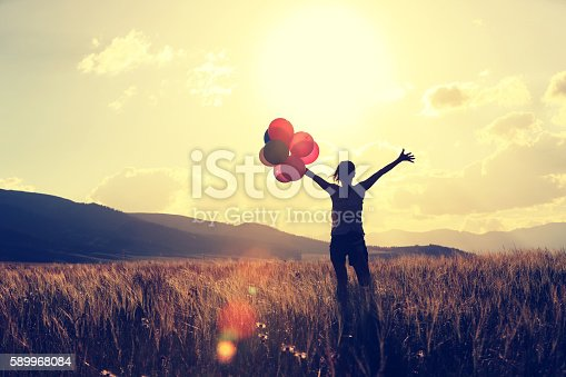 637457536 istock photo cheering young asian woman on grassland with colored balloons 589968084