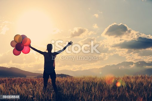 637457536 istock photo cheering young asian woman on grassland with colored balloons 594908848