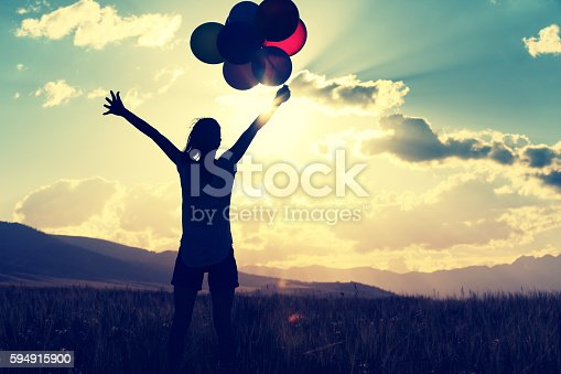637457536 istock photo cheering young asian woman on grassland with colored balloons 594915900
