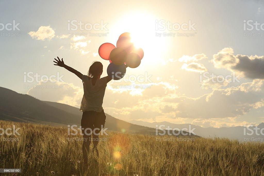 cheering young asian woman on grassland with colored balloons foto royalty-free