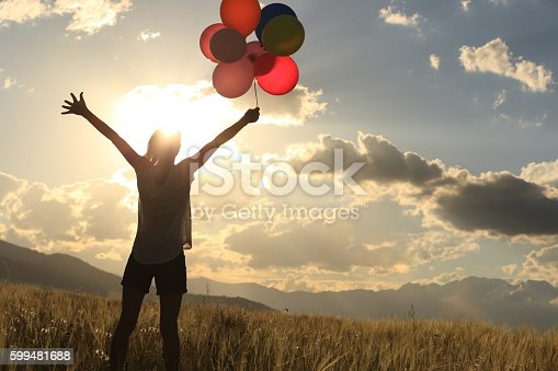 637457536 istock photo cheering young asian woman on grassland with colored balloons 599481688