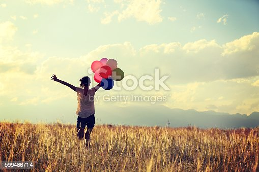 637457536 istock photo cheering young asian woman on grassland with colored balloons 599486714