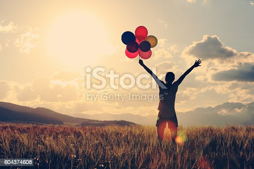 637457536 istock photo cheering young asian woman on grassland with colored balloons 604374608