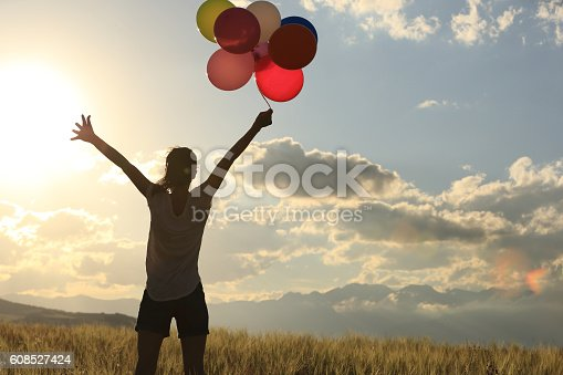 637457536 istock photo cheering young asian woman on grassland with colored balloons 608527424