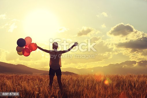 637457536 istock photo cheering young asian woman on grassland with colored balloons 638187924
