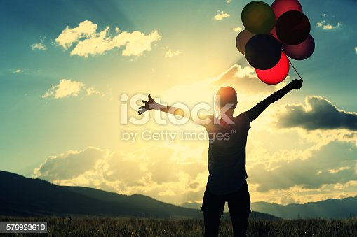 637457536 istock photo cheering young asian woman on sunset grassland with colored balloons 576923610