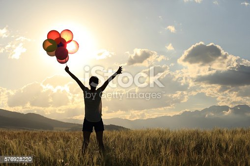 637457536 istock photo cheering young asian woman on sunset grassland with colored balloons 576928220