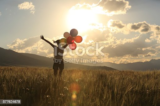 637457536 istock photo cheering young asian woman on sunset grassland with colored balloons 577624678