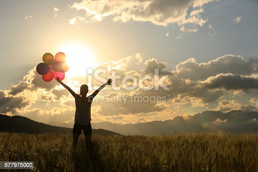 637457536 istock photo cheering young asian woman on sunset grassland with colored balloons 577975002