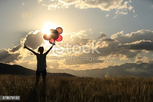 637457536 istock photo cheering young asian woman on sunset grassland with colored balloons 578079132
