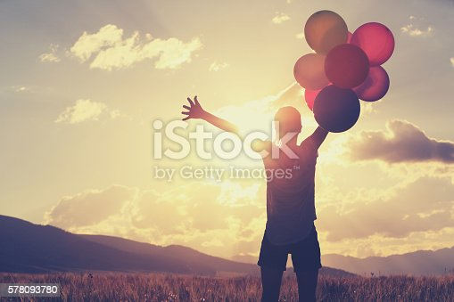 637457536 istock photo cheering young asian woman on sunset grassland with colored balloons 578093780