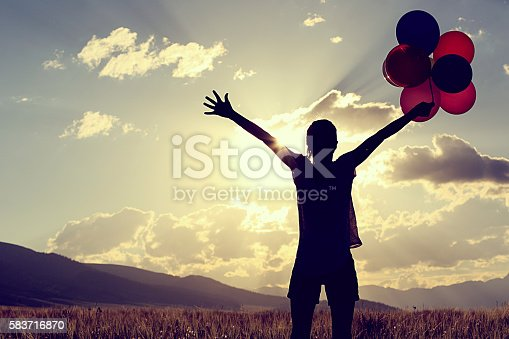 637457536 istock photo cheering young asian woman on sunset grassland with colored balloons 583716870