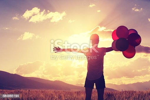 637457536 istock photo cheering young asian woman on sunset grassland with colored balloons 584885194