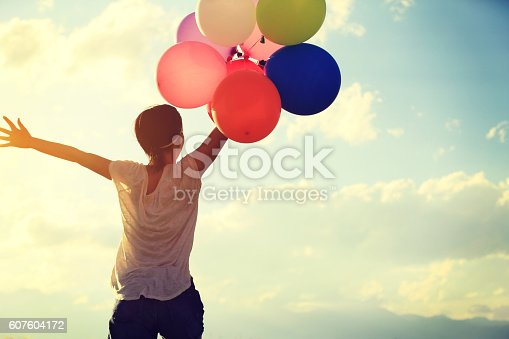 637457536 istock photo cheering young asian woman on sunset grassland with colored balloons 607604172