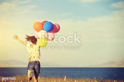 637457536 istock photo cheering young asian woman on sunset grassland with colored balloons 607611922