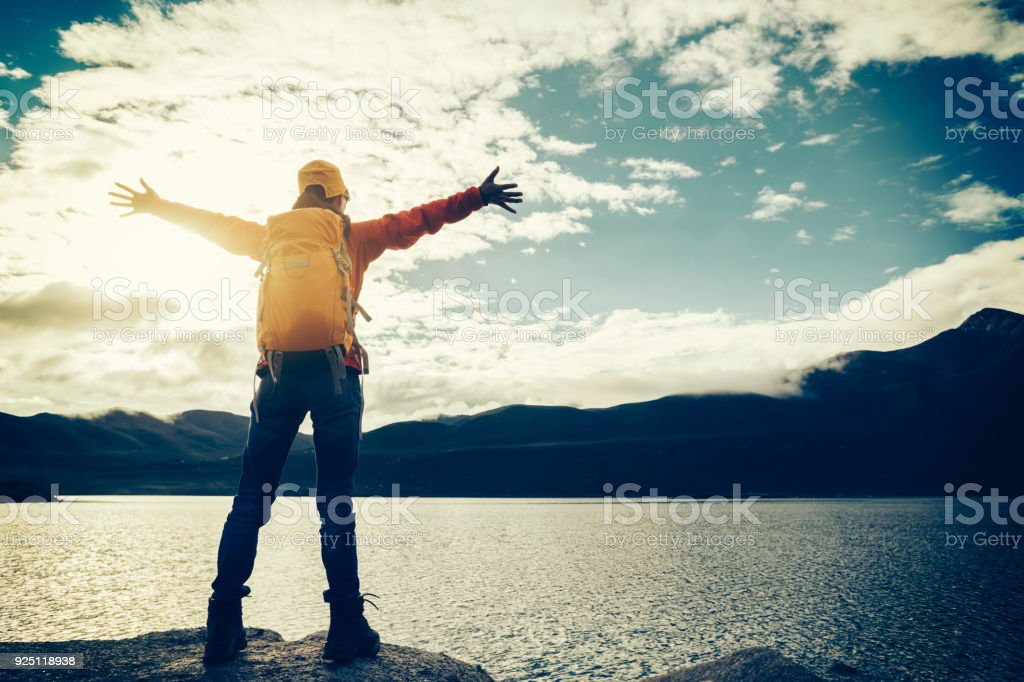 cheering young backpacking woman hiker outstretched arms face the mountains on waterside