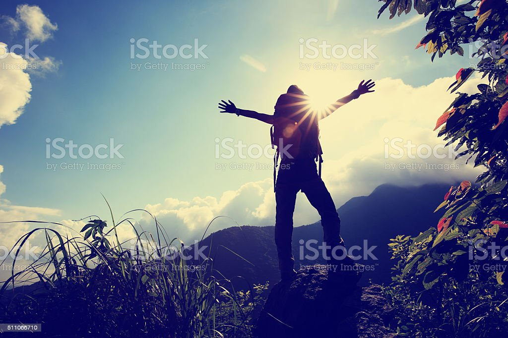 cheering young woman hiker open arms at sunrise mountain peak stock photo