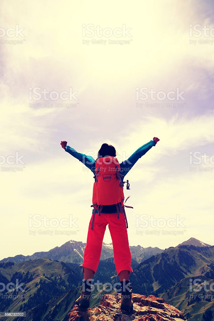 cheering young woman hiker open arms on mountain top foto royalty-free