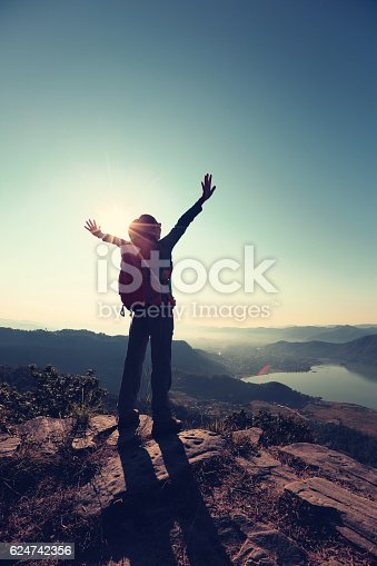 istock cheering young woman hiker open arms to the sunrise 624742356