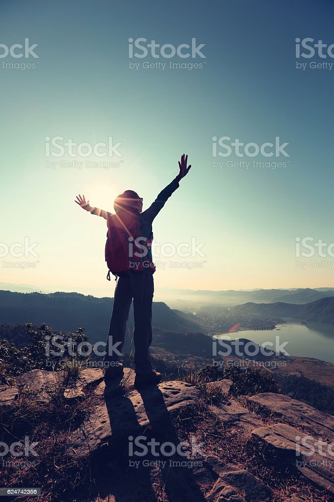 cheering young woman hiker open arms to the sunrise stock photo