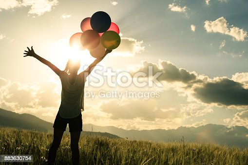 istock Cheering young woman jumping on grassland with colored balloons 883630754