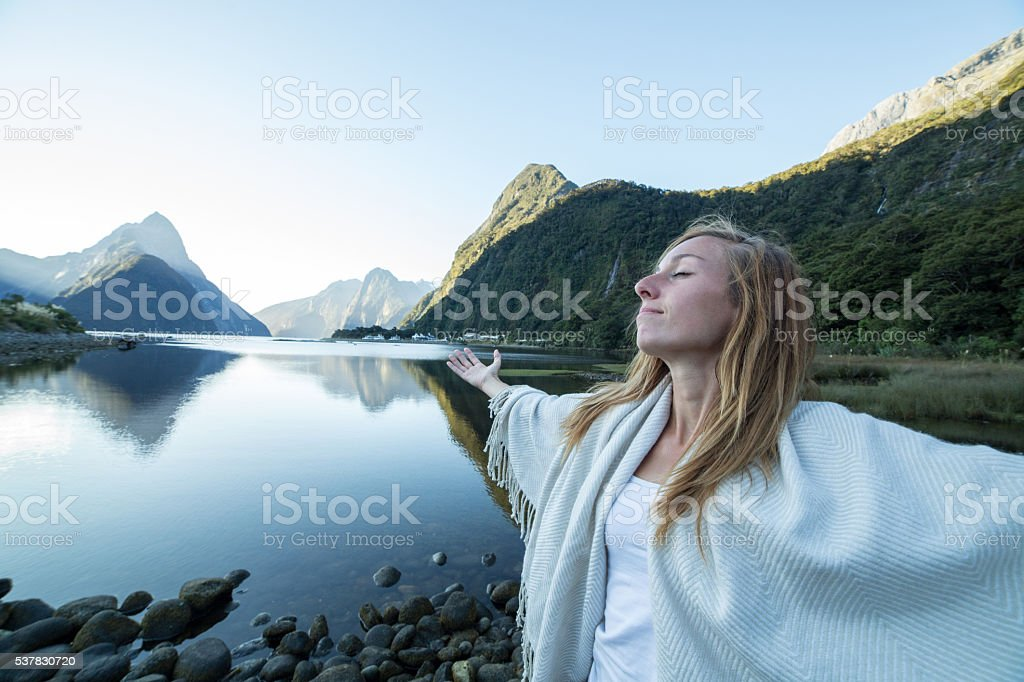 Cheering young woman stands arms outstretched at Mitre peak-Milford sound stock photo