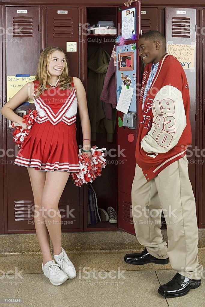Cheerleader and baseball player by lockers stock photo