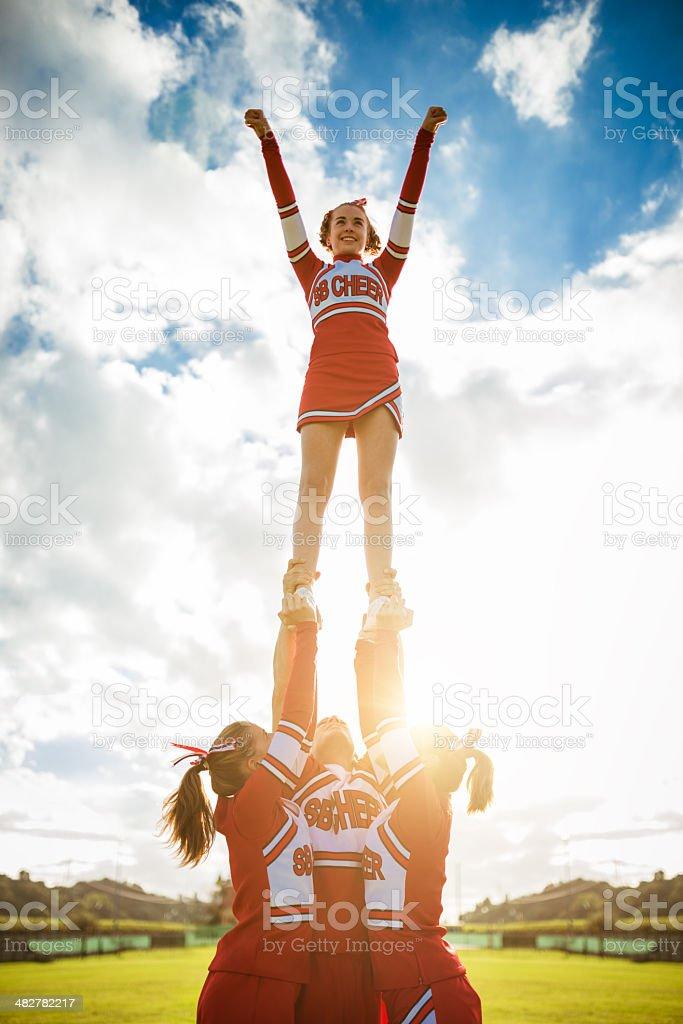 Cheerleader girl on top of the success stock photo