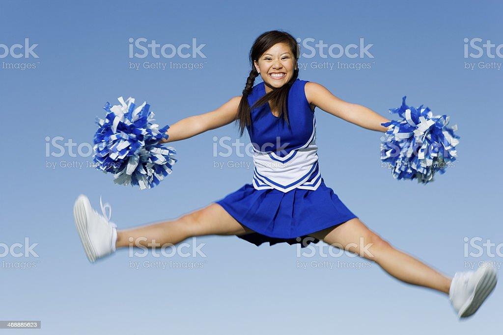 Cheerleader Performing Cheer in Mid-Air stock photo